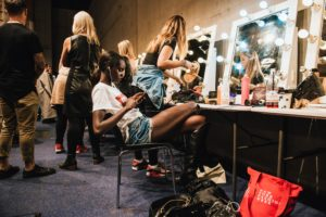 Person sitting behind the scenes of a fashion show