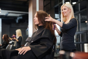 Woman doing another woman's hair in a salon
