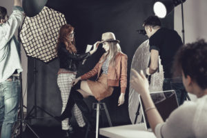 Woman fixing a model's look on set