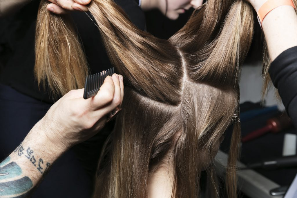 multiple people combing and styling a woman's hair