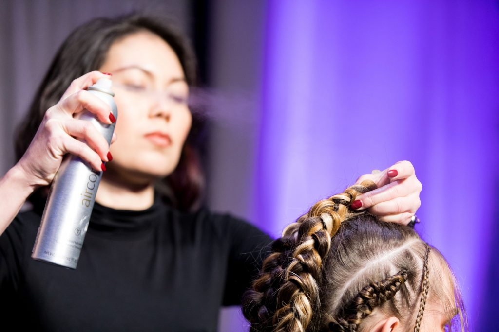 woman spraying hairspray onto another woman's braids
