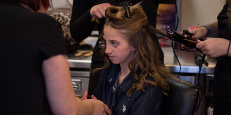 Young girl getting makeover by Douglas J students