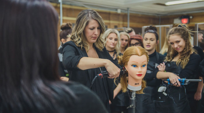 Woman instructing a class with a mannequin head