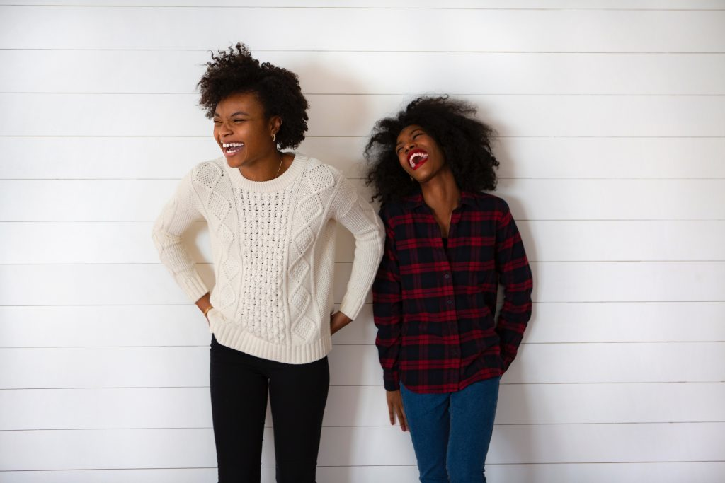 Two girls standing by a wall and laughing