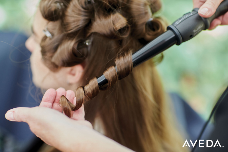 aveda editorial stylist curling a model's hair