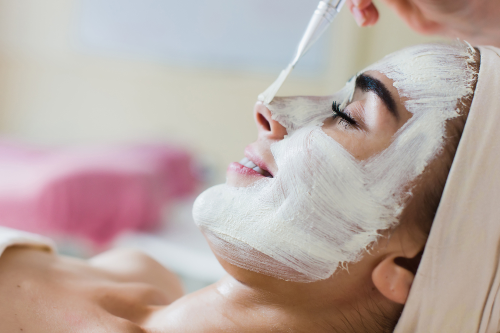 woman smiling while getting a facial
