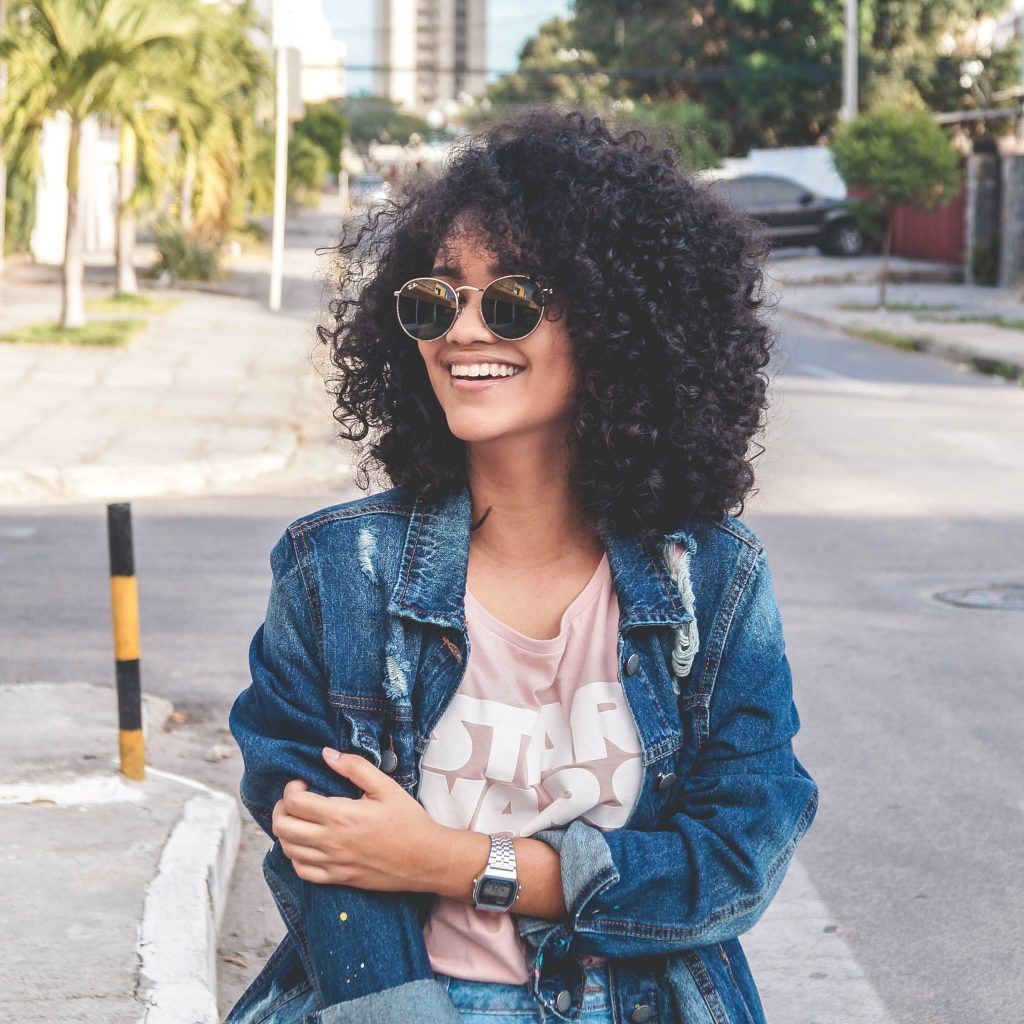 Woman with curly hair standing outside during summer