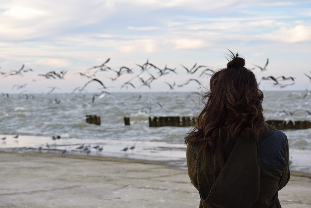 Brunette woman seen from behind stands in front of the ocean