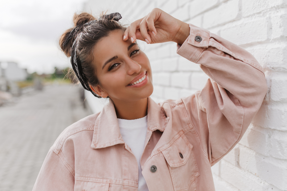 Woman wearing headband and pink jacket leaning against wall outside