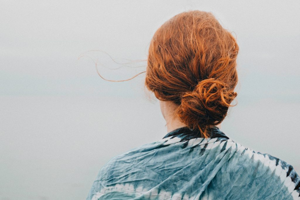 Red haired woman with low hair bun from behind