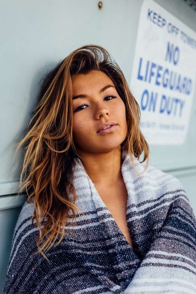 Woman with wavy hair wearing blanket outside lifeguard stand