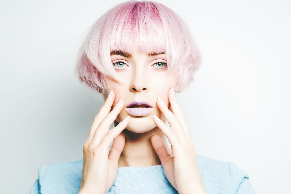 model with short light pink hair looking at the camera with hands on face