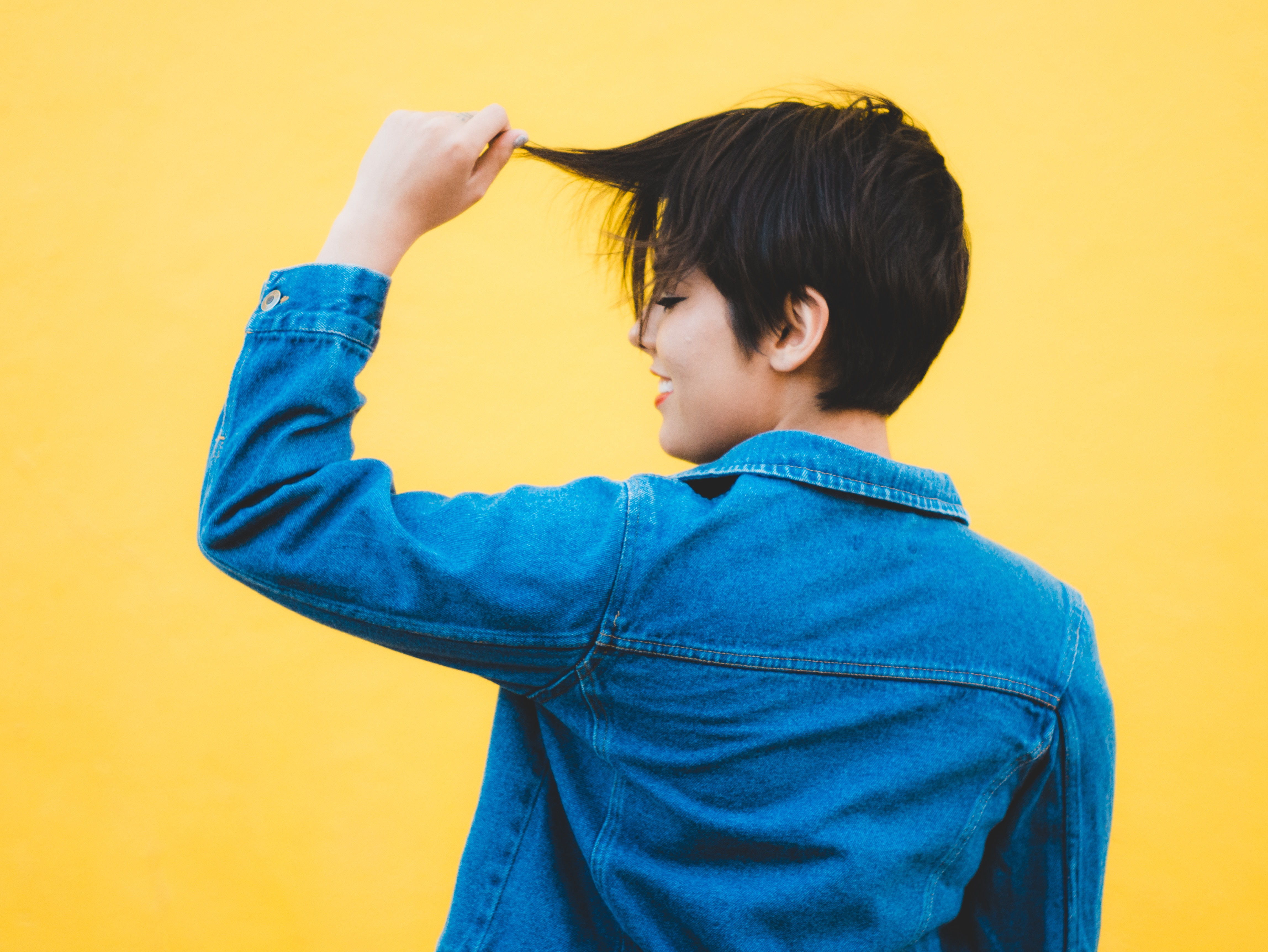 asian model on yellow background playing with short hair