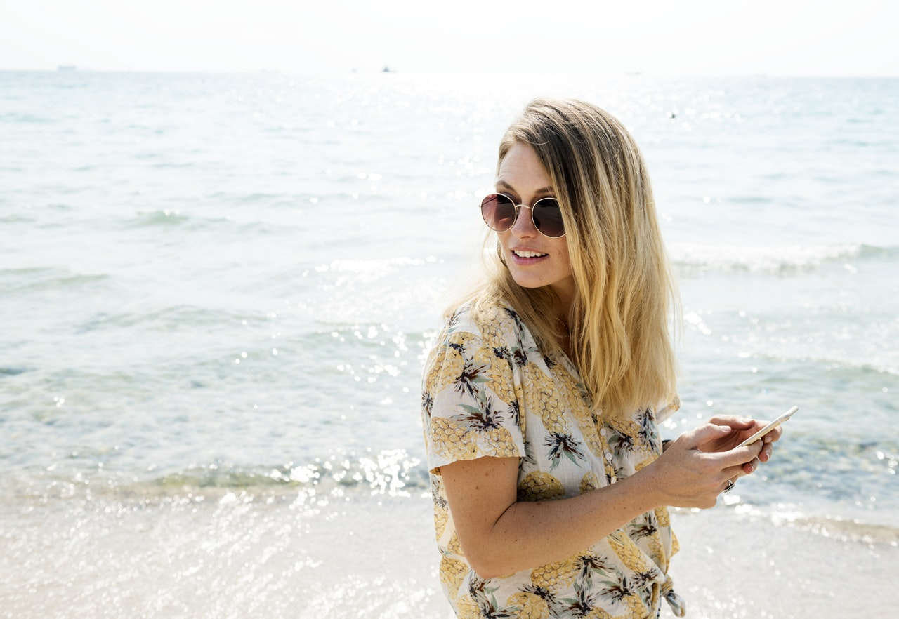 girl wearing a pineapple shirt texts at the beach