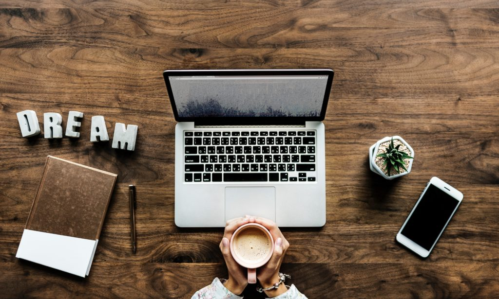 blogger working at a desk with coffee and an iphone