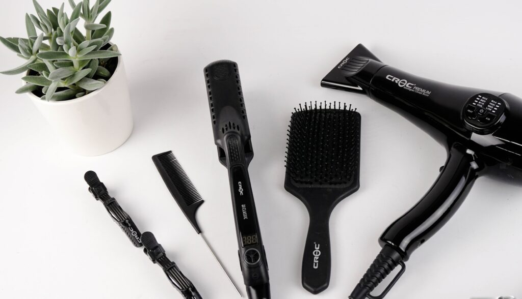 Hot styling tools next to a brush and comb.