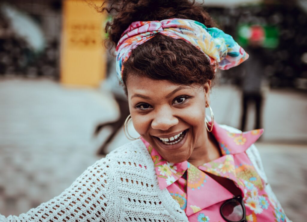 Smiling woman with a colorful outfit.