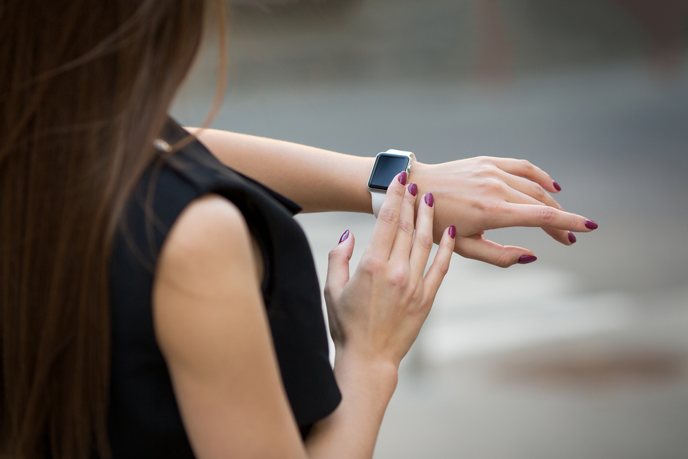 Woman checking a smart watch.