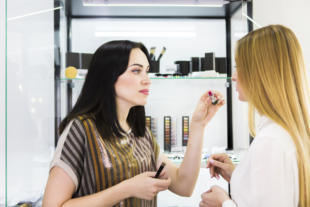 beauty consultant working with a client to find the right lipstick color