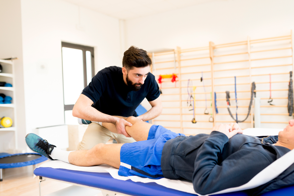 Male message therapist massaging a client's thigh