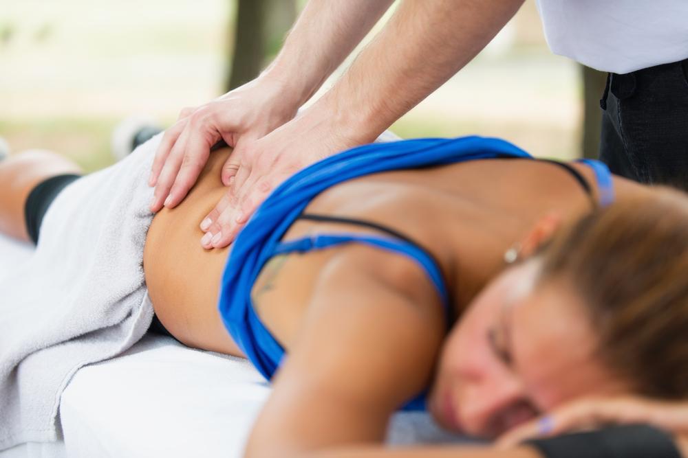 Massage therapist massaging a female client