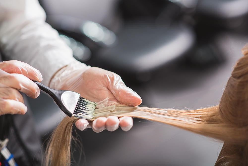 hairstylist applying hair color to blonde strands