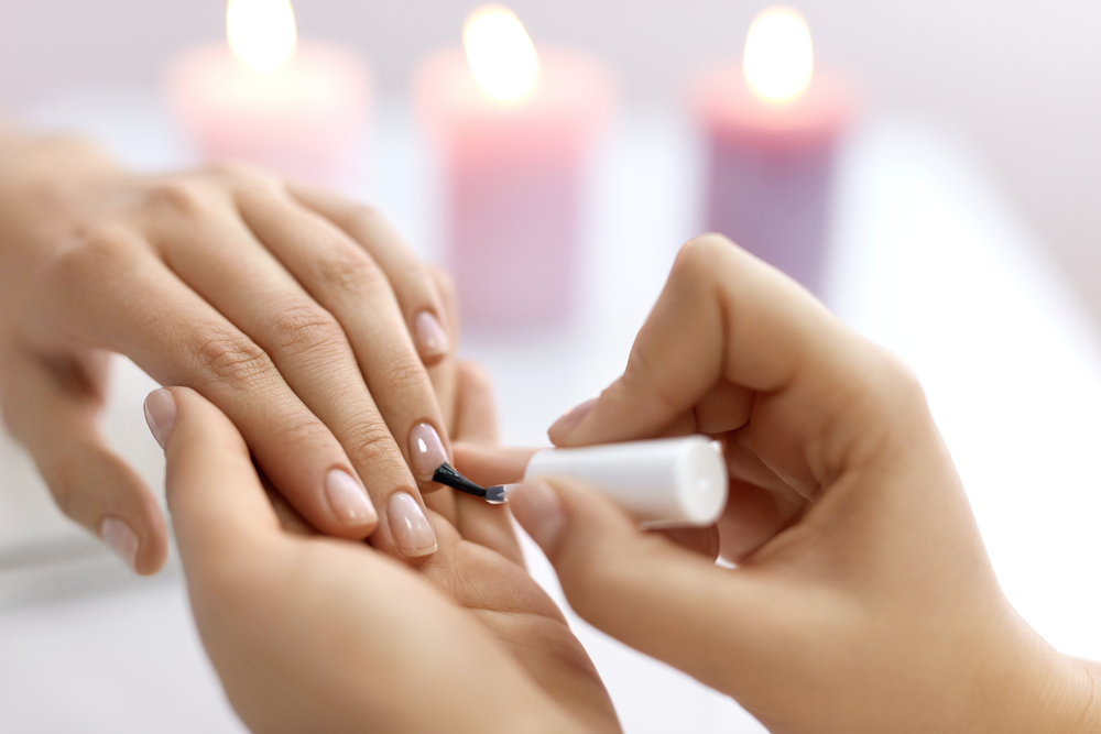 cosmetologist performing a manicure
