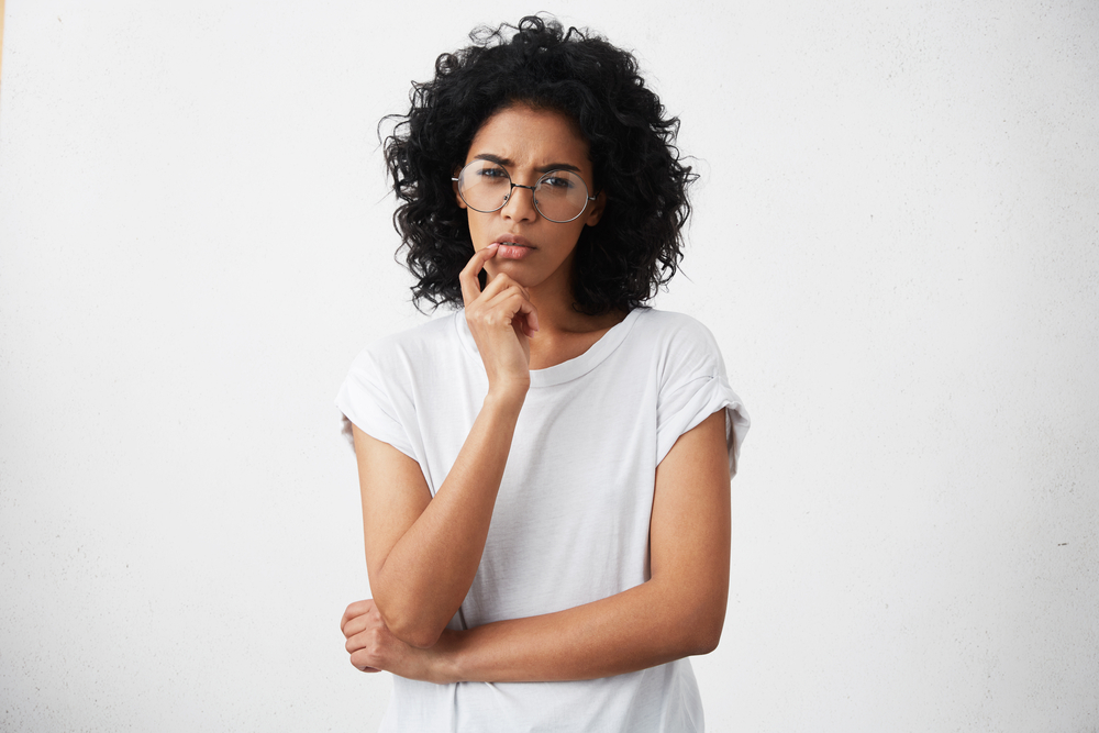 black woman wearing glasses and thinking
