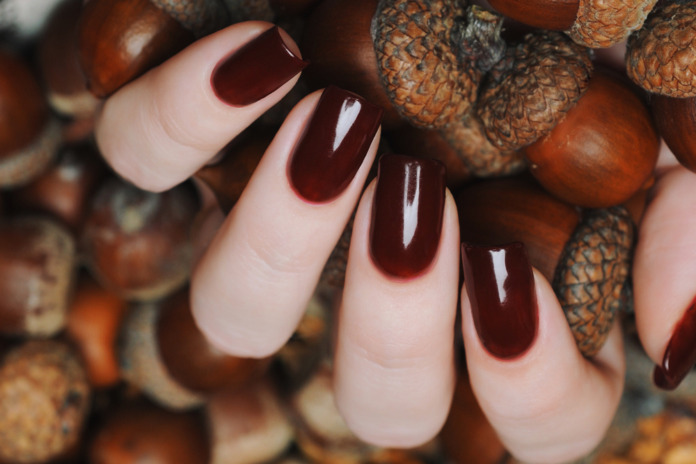 fingers with a maroon nail polish