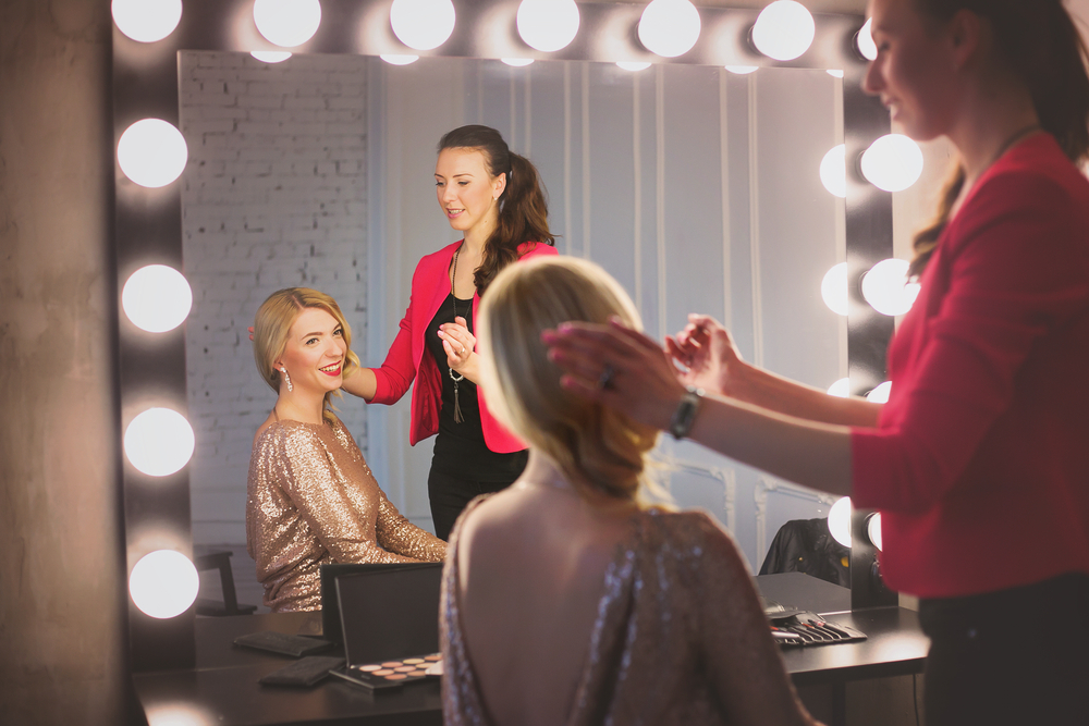 Woman looking at her hair in a dressing room mirror