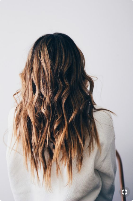 Blonde woman with beachy waves in her hair.