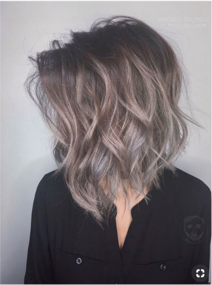 Woman with greyish blonde bob wears it in beach waves.