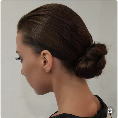 Brunette woman with a sleek low bun.