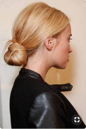 Blonde woman in a leather jacket wears a low bun.