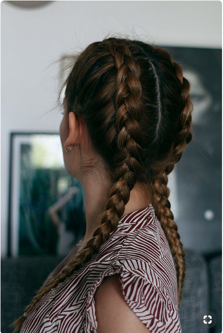 Woman with ombre brunette hair wears boxer braids.
