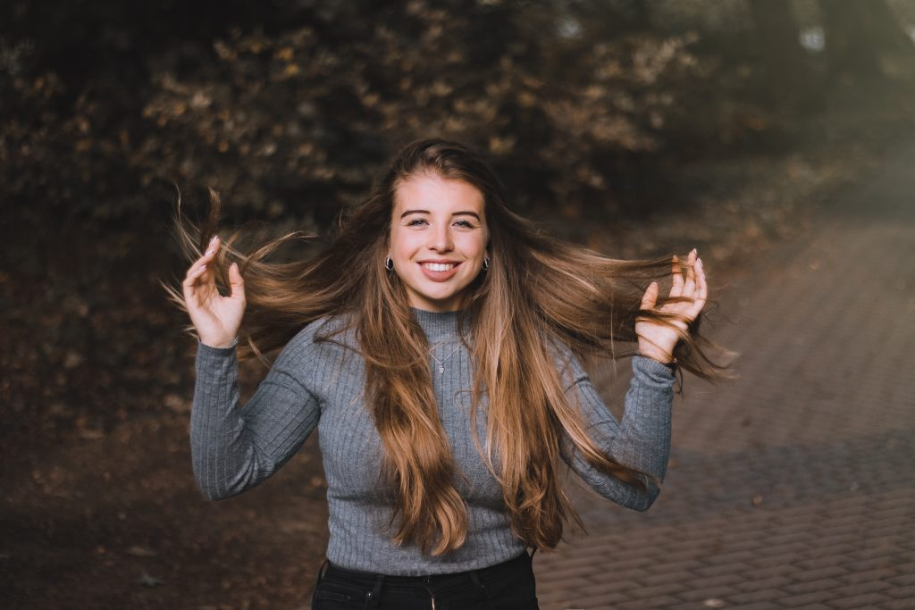 girl holding her hair and blowing in the wind