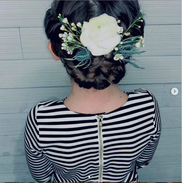 Shot of a woman in a striped shirt with floral wedding hair.