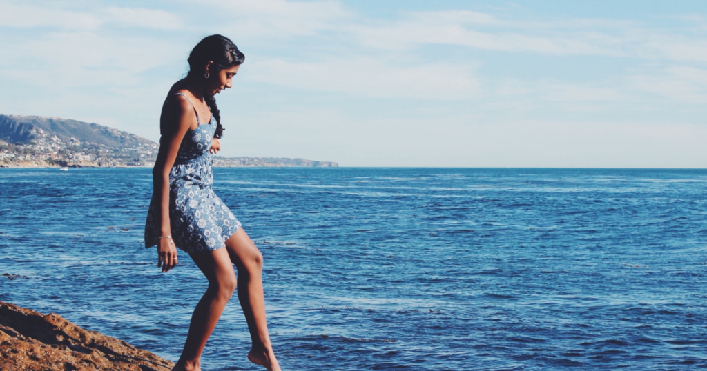 Beautiful woman in a blue romper tips her toe in the sea.