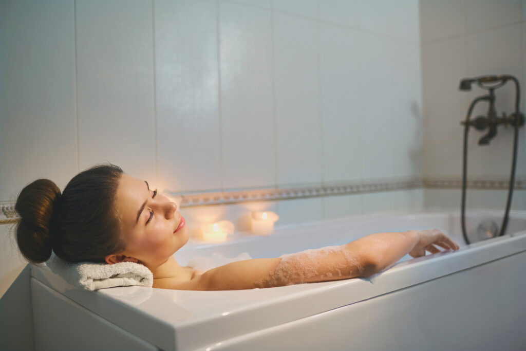 Girl soaking in a bathtub with candles.