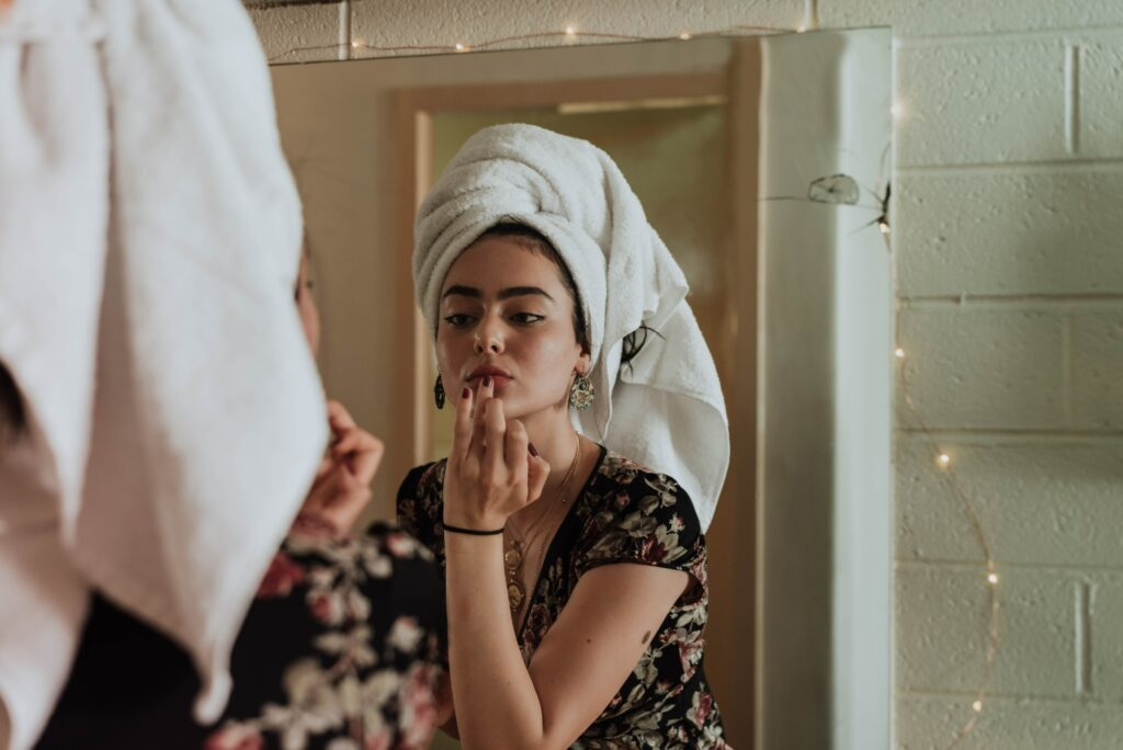 Girl with a towel on her head doing skincare routine.