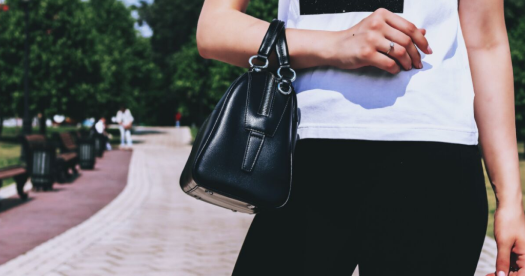 Close-up of a woman standing outside with a black purse on her arm