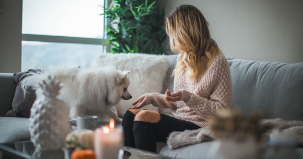 Girl sitting on a couch with her dog, surrounded by candles.