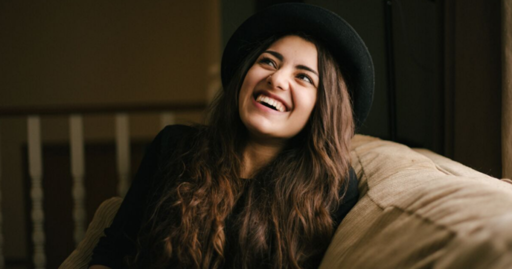 Smiling girl with a black hat.