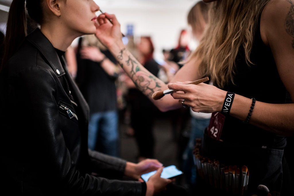 Makeup artist does a guest's makeup backstage.