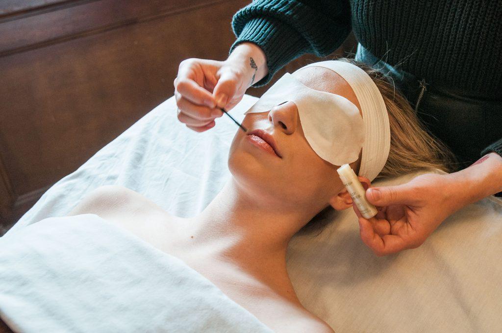Esthetician gives a client a facial treatment.