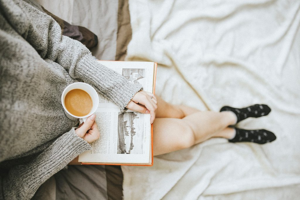 Woman in grey sweater sitting on a bed with a hot drink.