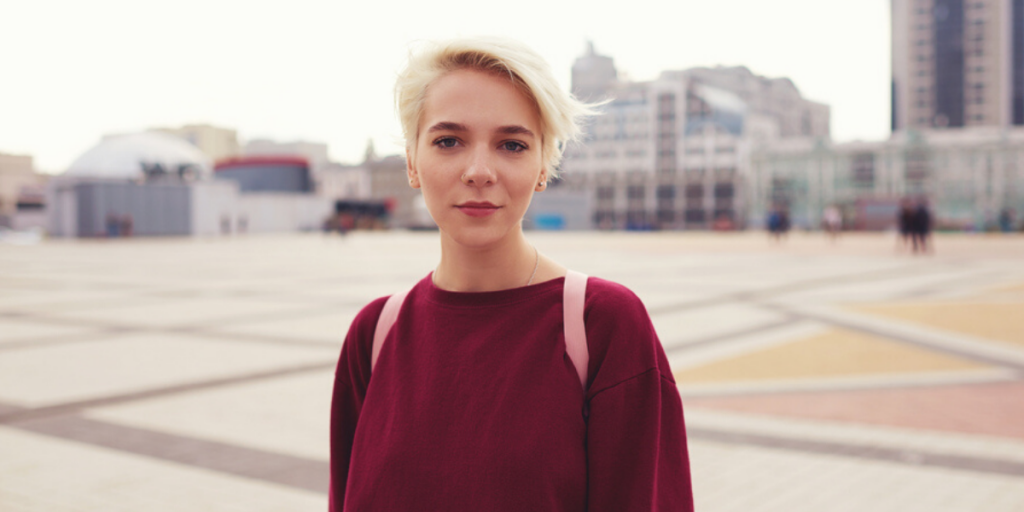 Girl with blonde pixie cut wearing a red sweater.