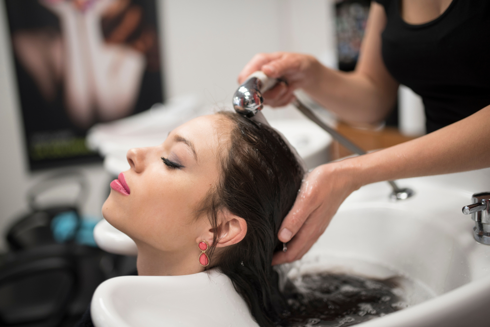 Hair stylist washing a client's hair.