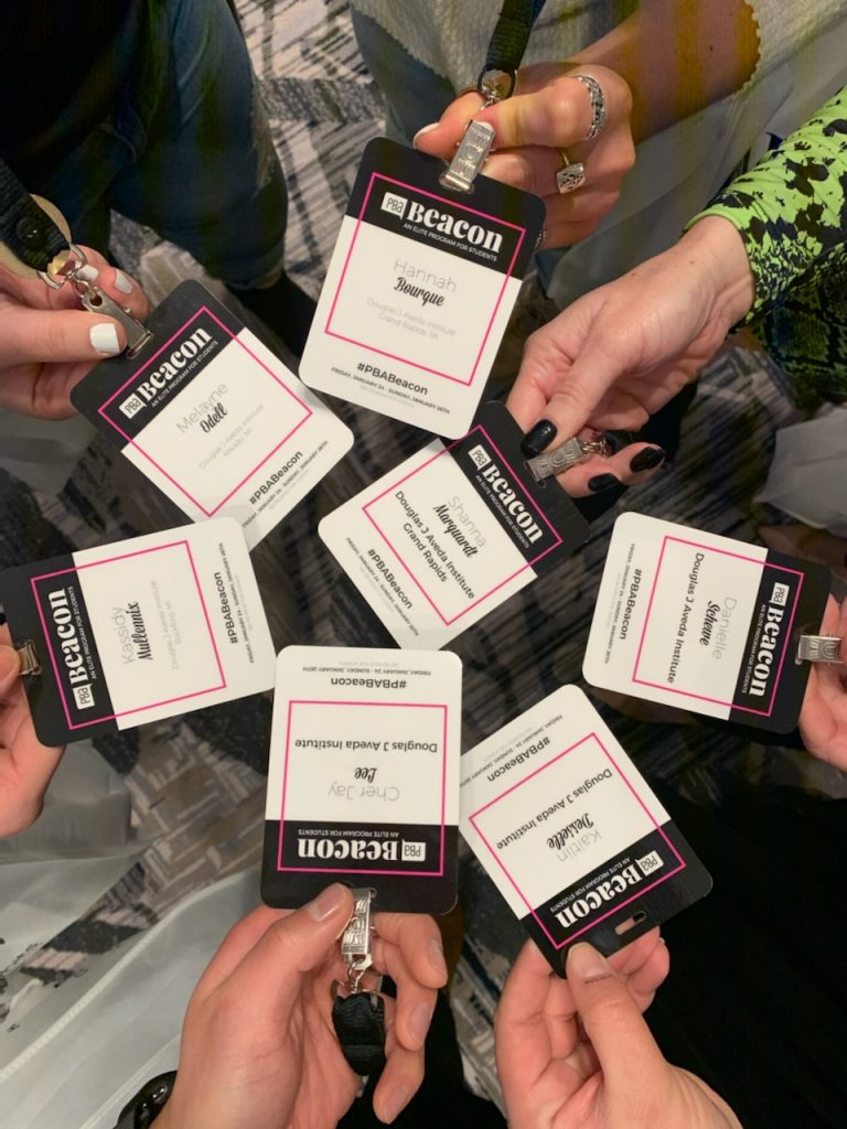 hands holding name tags at the beacon awards program