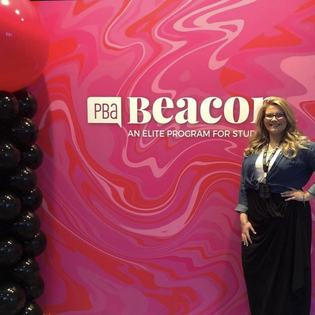 "a blonde woman standing in front of a pink wall that reads ""PBA Beacon Awards"""